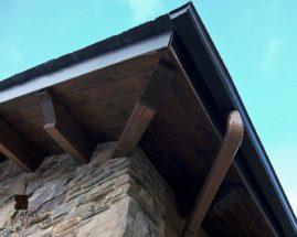 Foto de detalle de aleros de cubierta formados por panel de madera para cubierta con núcleo aislante.